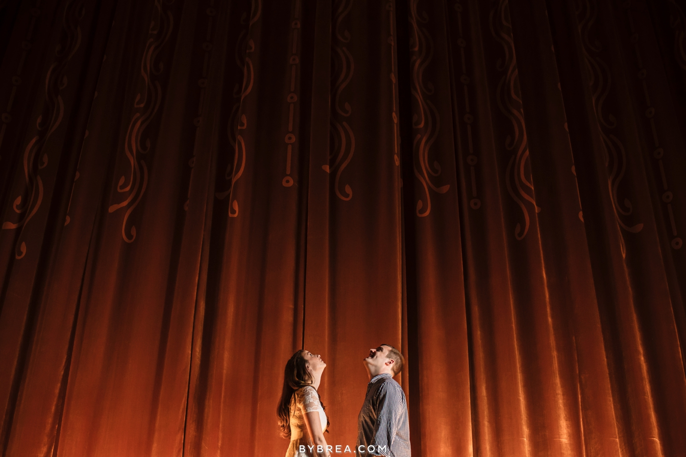 Senator Theater engagement couple looks up in front of curtain