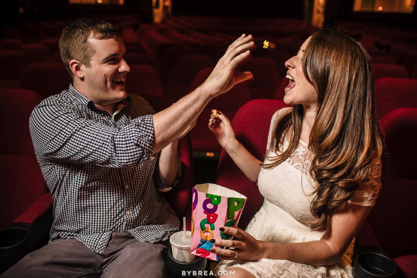Senator Theater Baltimore engagement couple throwing popcorn