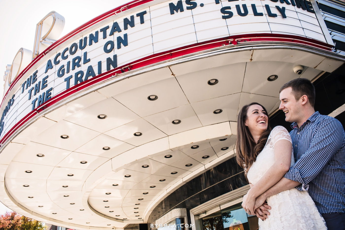 Senator Theater engagement couple stands under marquee