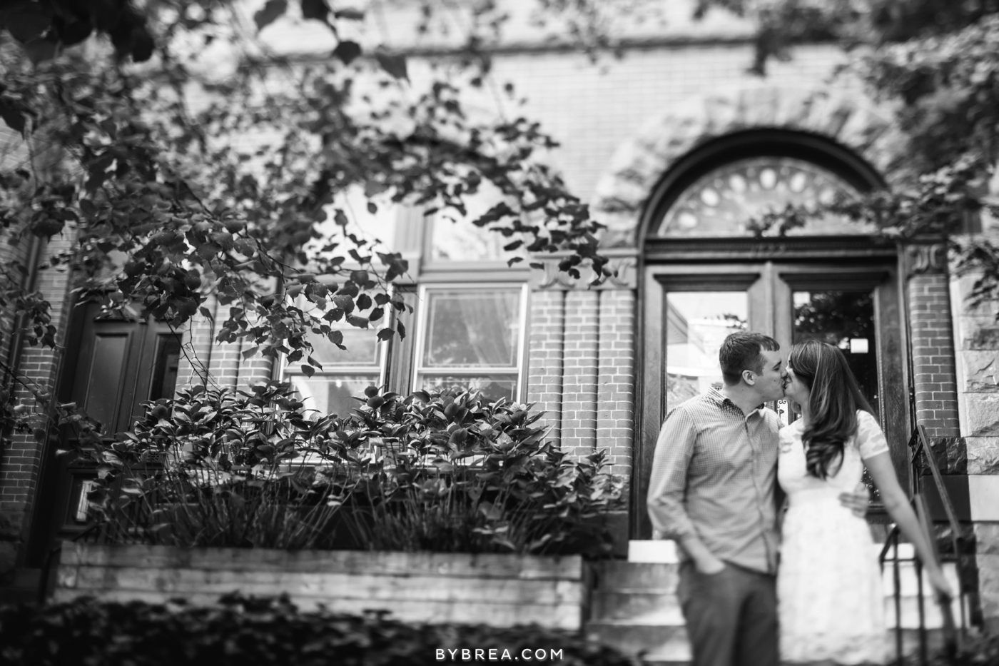 Baltimore engagement photo couple kissing in front of building