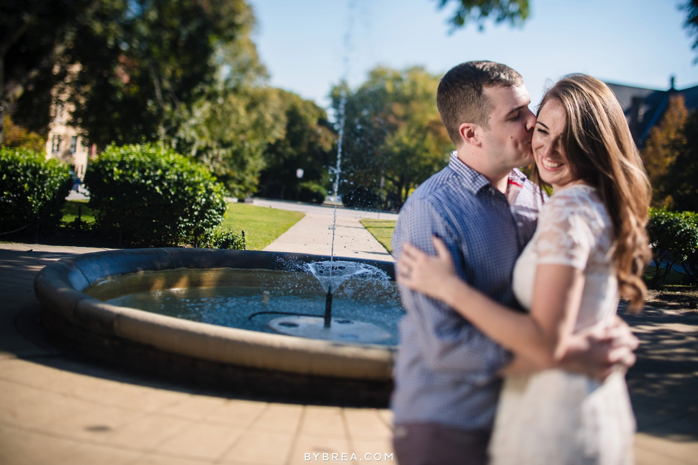 Baltimore engagement man kisses woman's cheek in front of fountain