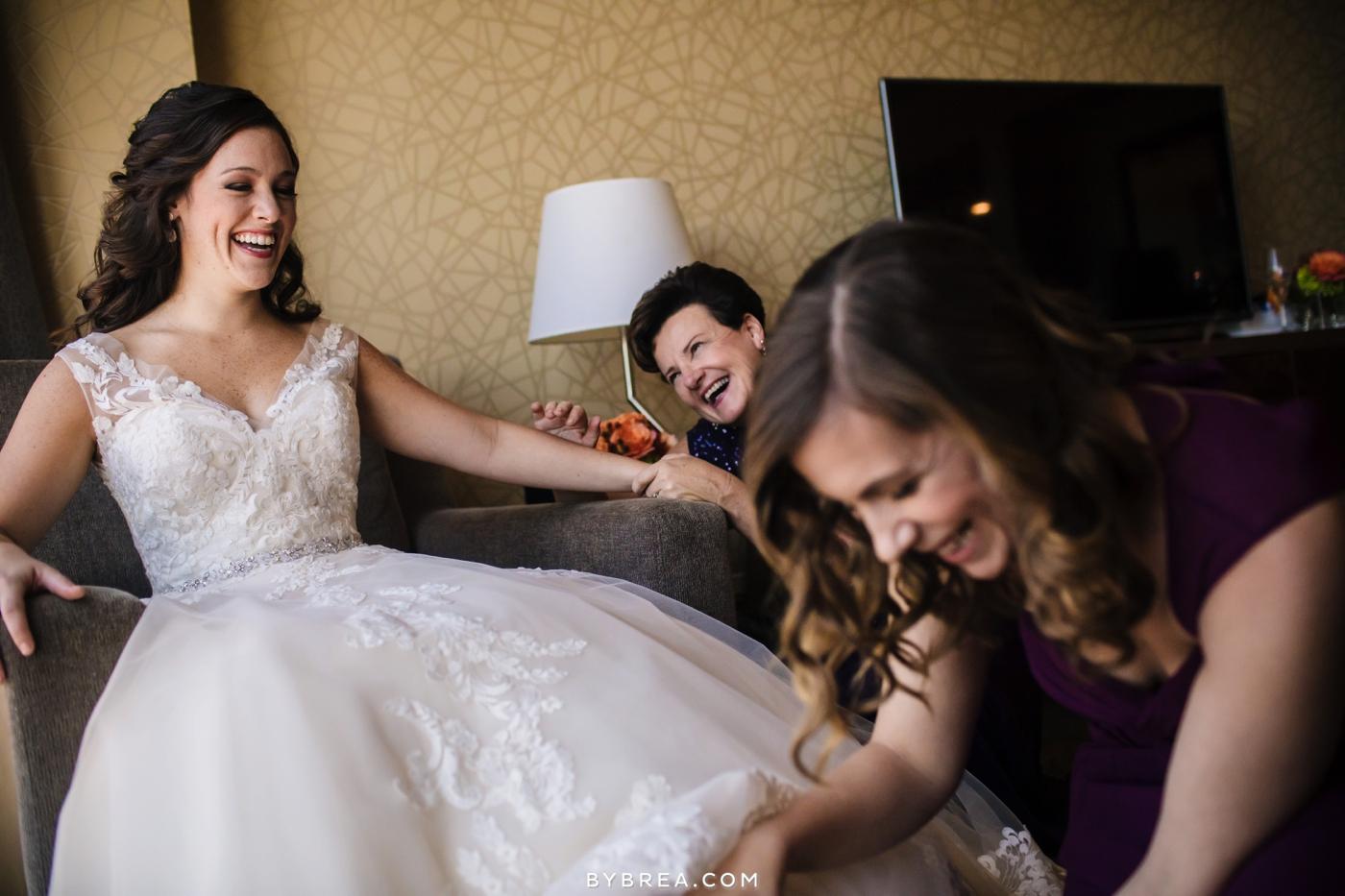 Baltimore wedding bride laughing having shoes put on