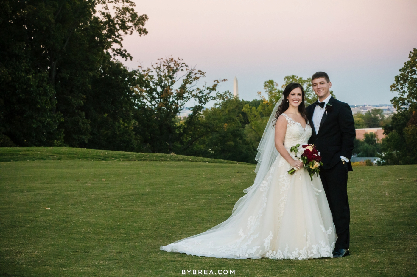 Bride and groom on green lawn with Washington monument