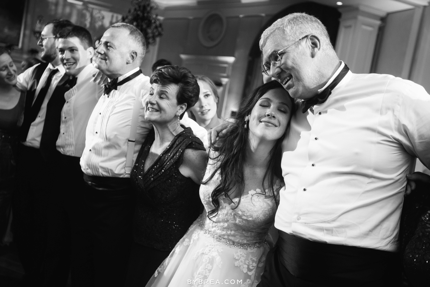 Baltimore wedding guests leaning on each other smiling