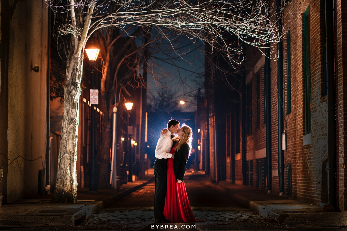 Christmas themed engagement session photo fancy couple kissing at night portrait