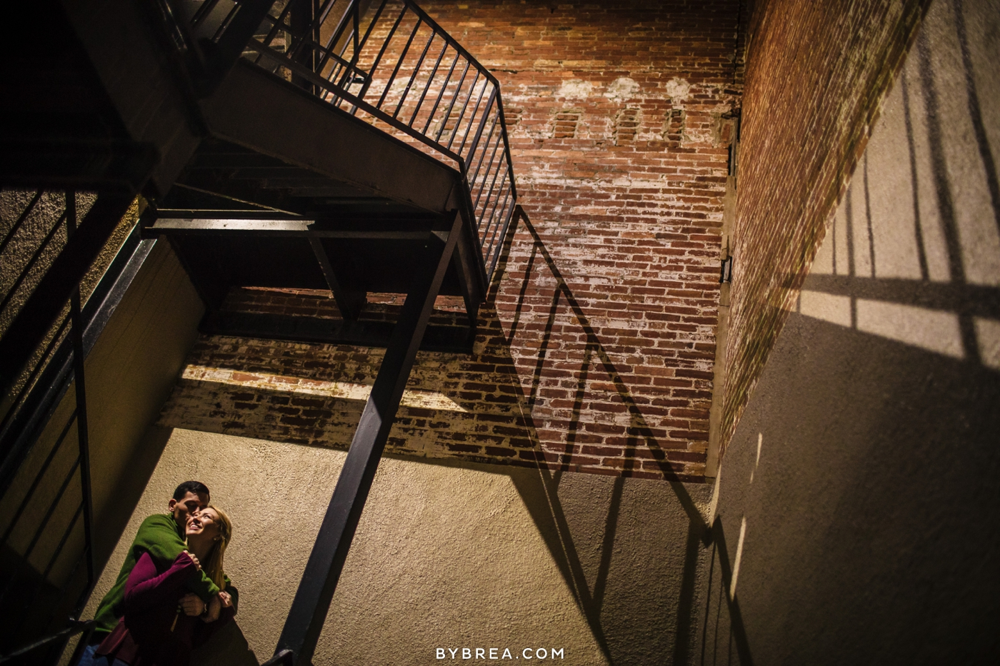 Baltimore engagement session photo couple under stairs exposed brick
