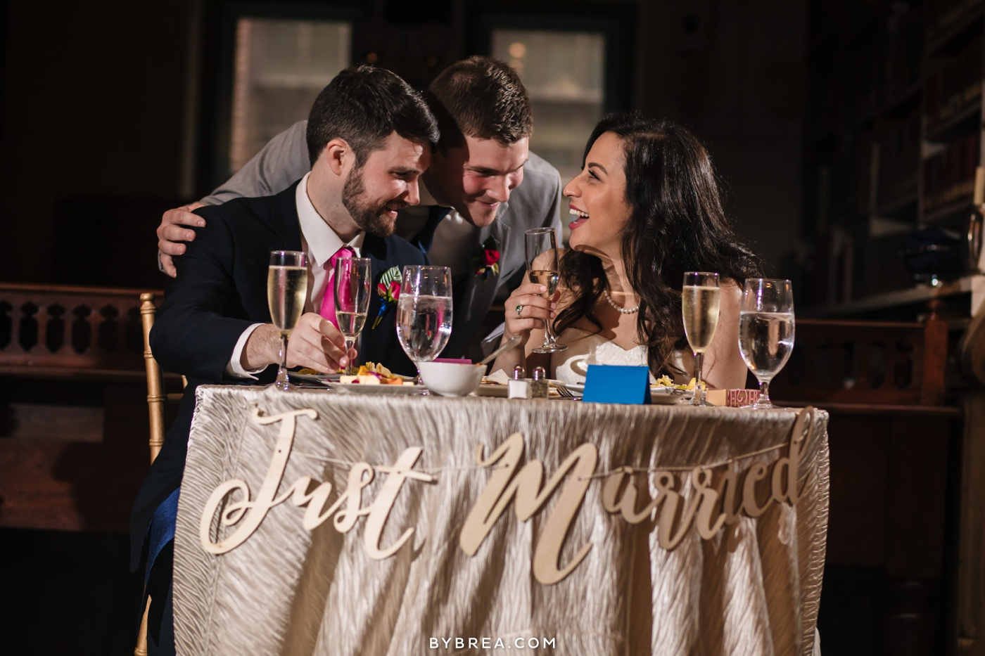 George Peabody Library wedding photo couple at sweetheart table laughing with best man