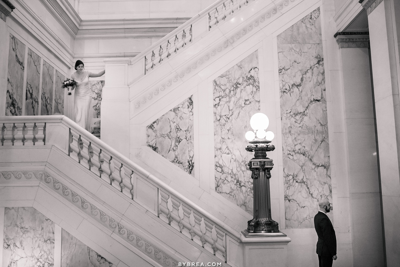 Photograph of bride coming down the stairs first look Baltimore wedding Hotel Monaco