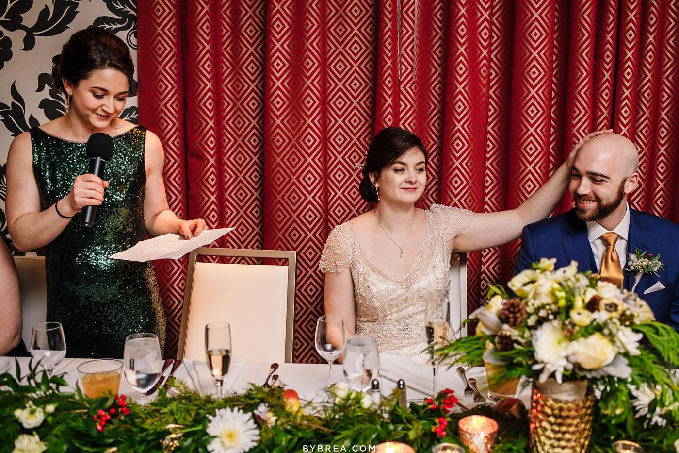 Photo of bride rubbing grooms head during speeches Baltimore wedding
