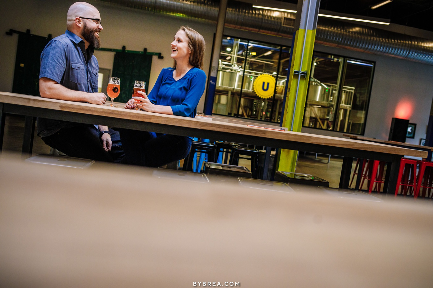 couple enjoying beer during engagement shoot at Union Collective