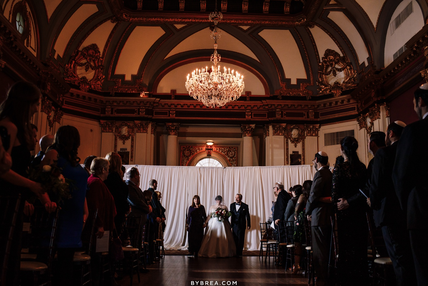 Photo of bride walking down the aisle during wedding ceremony on 12th floor at the Belvedere in Baltimore.