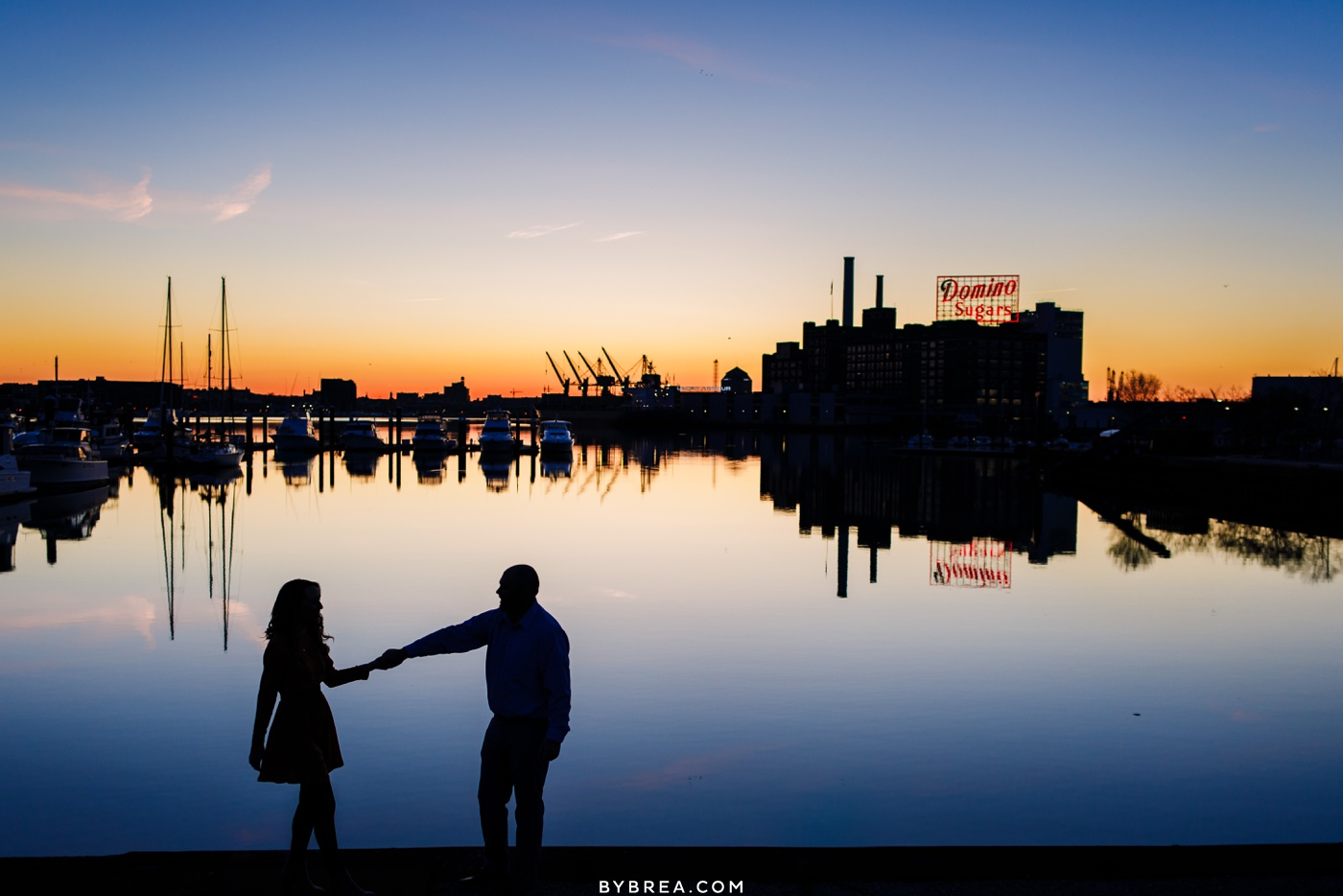Sunrise silhouette engagement photo Domino Sugar sign Fed Hill