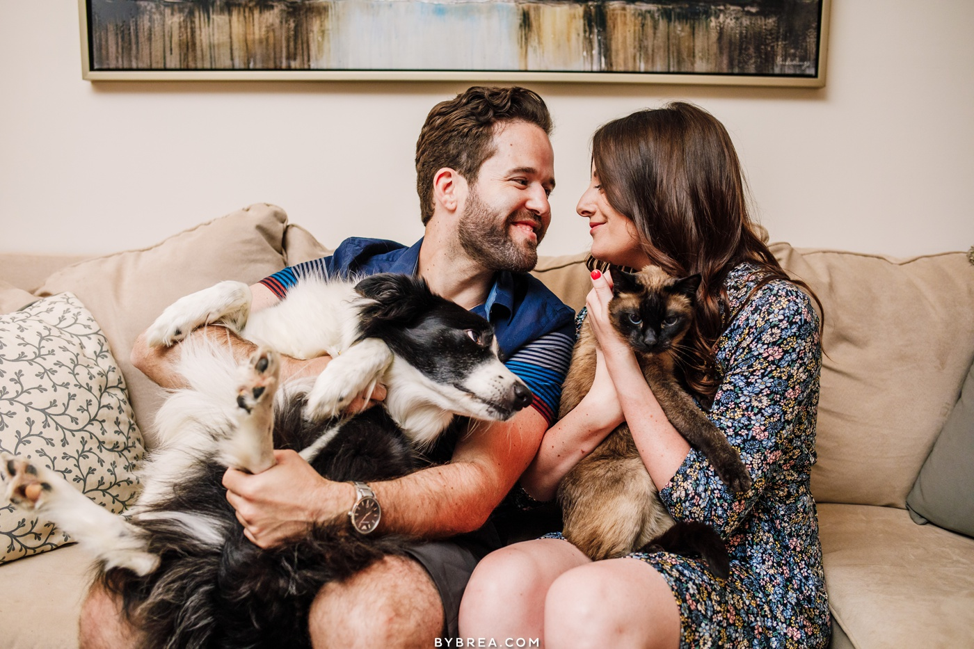Lifestyle engagement photo of couple enjoying pet friends in their home