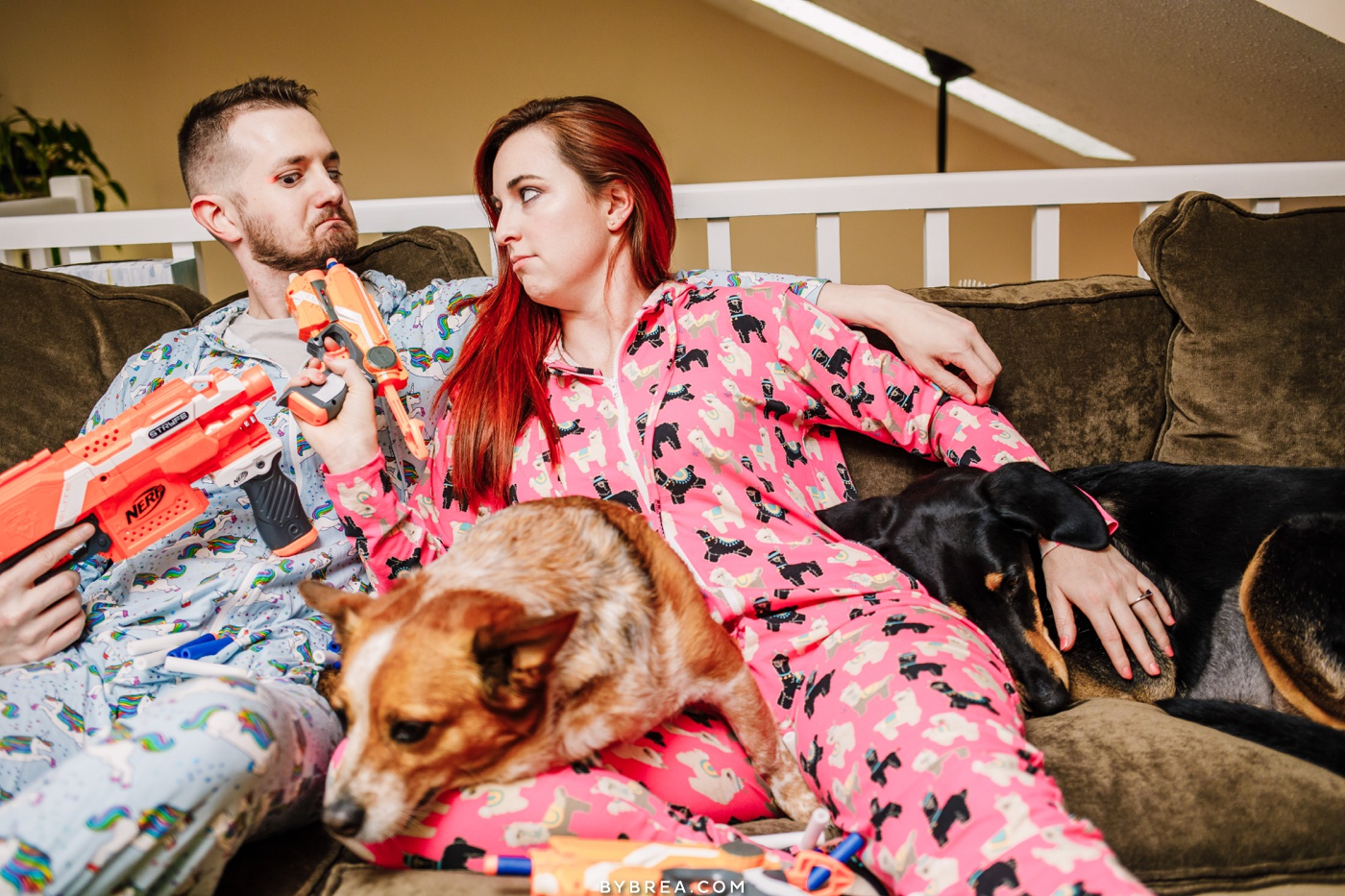 Lifestyle engagement photo of couple playing with nerf guns while wearing meundies onesies and puppies snuggling