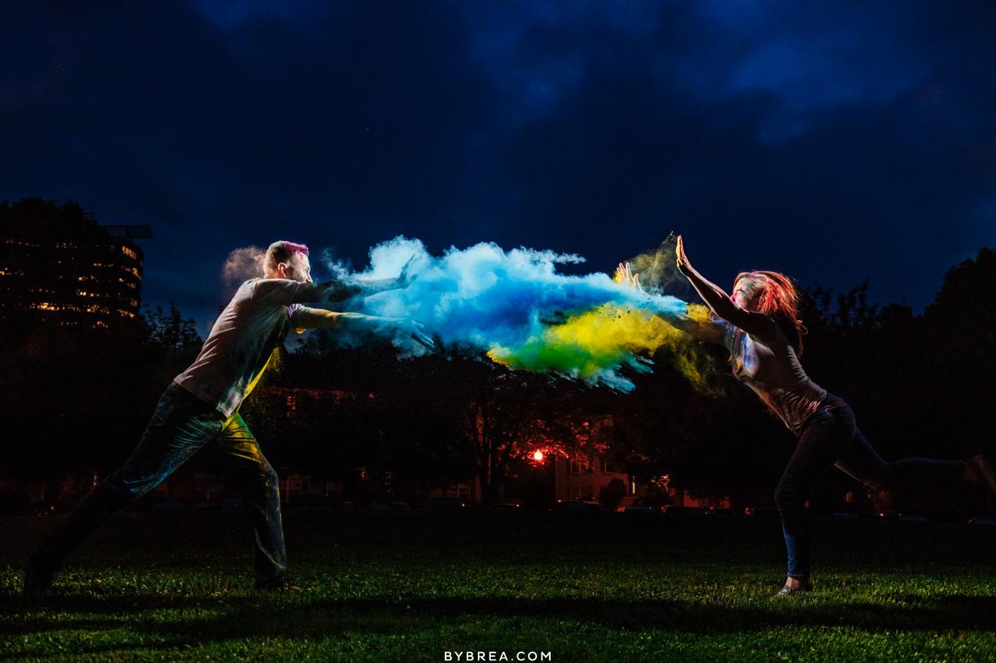 Baltimore engagement photo of couple having paint powder fight creative lighting night time shot