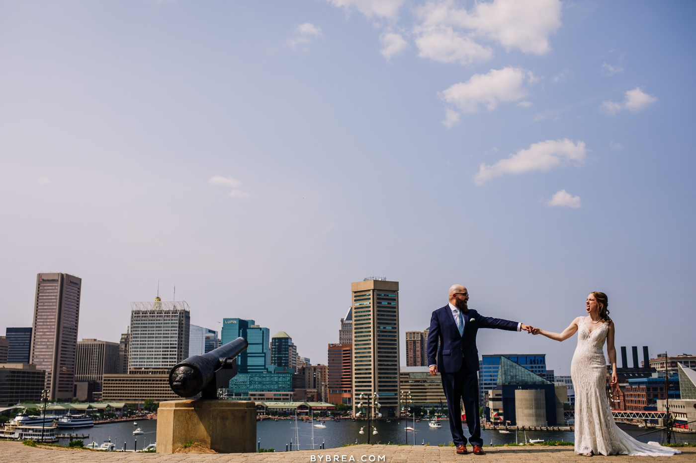 Photo of bride and groom acting sill on Federal Hill during couples portraits Baltimore wedding