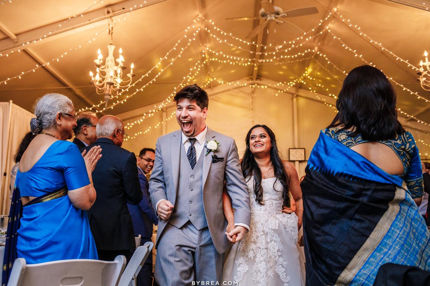 Elkridge Furnace Inn bride and groom walking into tent during reception.
