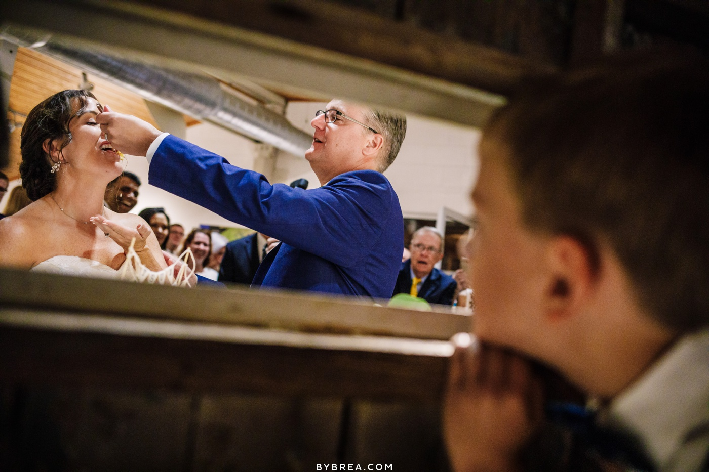 Cute picture of ring bearer watching the bride and groom cut the cake at wedding at the Annapolis Maritime Museum.