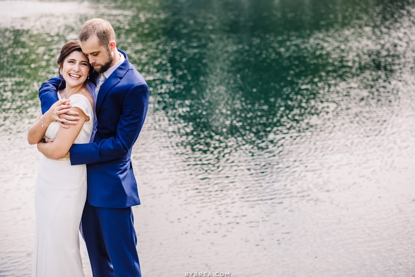 Bride and groom against colorful water at Pond View Farm