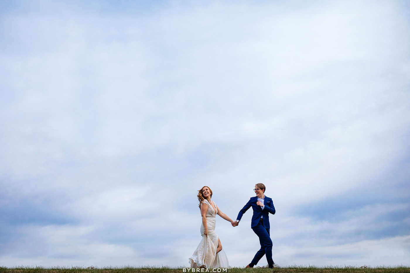 Candid moment of brides enjoying their wedding day during portraits at Tusculum Farm
