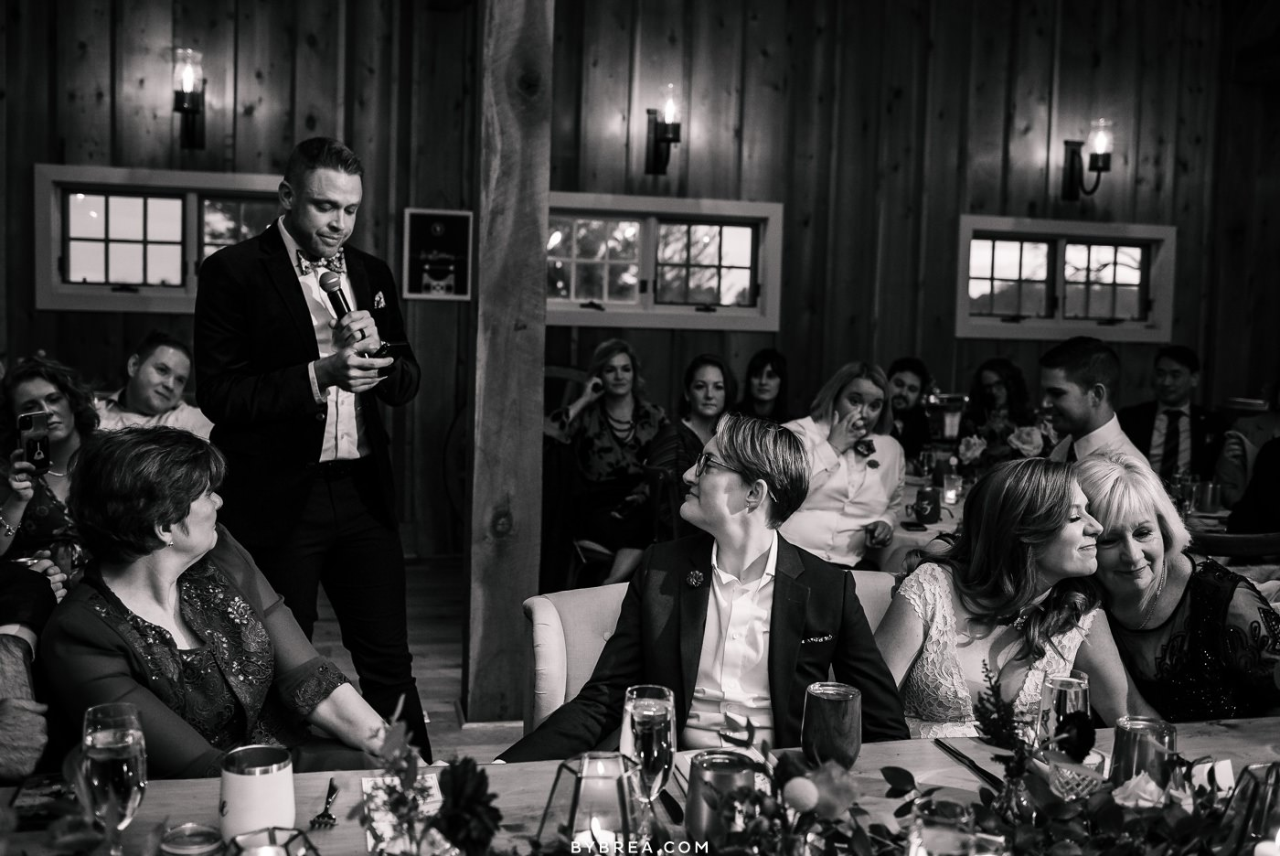 Emotional photo of brides embracing their moms during toasts at Tusculum Farms wedding