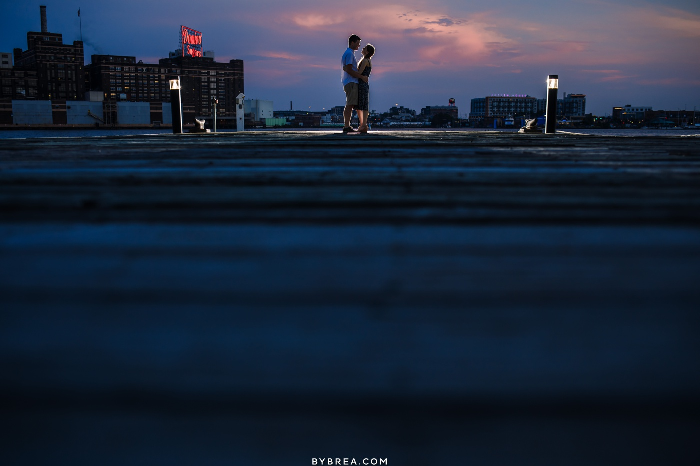 Fells Point engagement photo with Domino Sugars sign