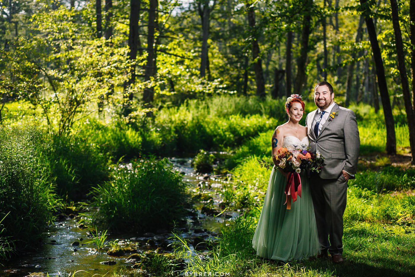 Portrait by creek at Caboose Farm Wedding
